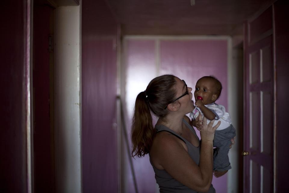 ,In this Nov. 13, 2013 photo Rhyan Buettner a volunteer, holds ten month old Martelly Jean Louis, in the U.S.-based Church of Bible Understanding orphanage in Kenscoff, Haiti. The orphanage is run by a Christian missionary group funded by the Olde Good Things antique store on Manhattan's Upper West Side. While many other orphanages also have failed the Caribbean country's new national standards, and conditions are far worse in some, the group's three-story building on the hilly outskirts of Port-au-Prince stands out because it's run by an organization with such an unusual, and successful fundraising operation. The failure to meet the standards would seem to contradict their financial position.(AP Photo/Dieu Nalio Chery)