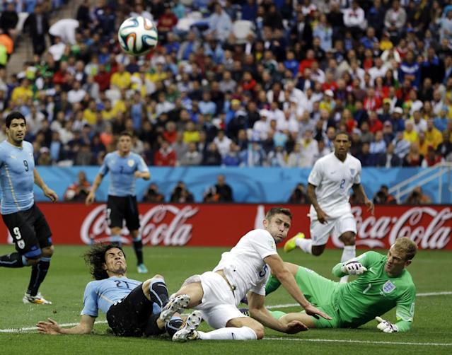 England's Gary Cahill kicks the ball away on an attack by Uruguay's Martin Caceres as England's goalkeeper Joe Hart protects the goal mouth during the group D World Cup soccer match between Uruguay and England at the Itaquerao Stadium in Sao Paulo, Brazil, Thursday, June 19, 2014. (AP Photo/Kirsty Wigglesworth)