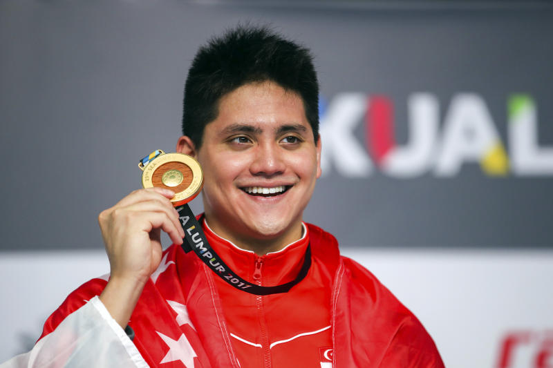 Singapore's Joseph Schooling smiles with his medal after winning the Men's 50M Butterfly Swimming final of the 29th South East Asian Games in Kuala Lumpur, Malaysia, Monday, Aug. 21, 2017. (AP Photo/Adrian Hoe)