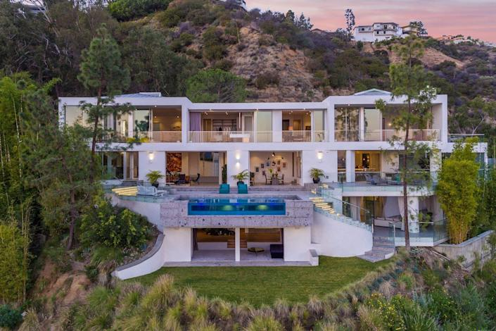 Located in the highly coveted Bird Streets area of the Hollywood Hills, this home, designed by Studio Dardo, offers panoramic views of the city below. The spacious home is filled with spaces for entertaining including a bar, outdoor lounges, and a sunken media room beneath the glass-bottomed infinity pool. The firm designed the house around a cork tree and used breccia, a volcanic stone, and wood flooring to add natural elements to the sleek spaces.