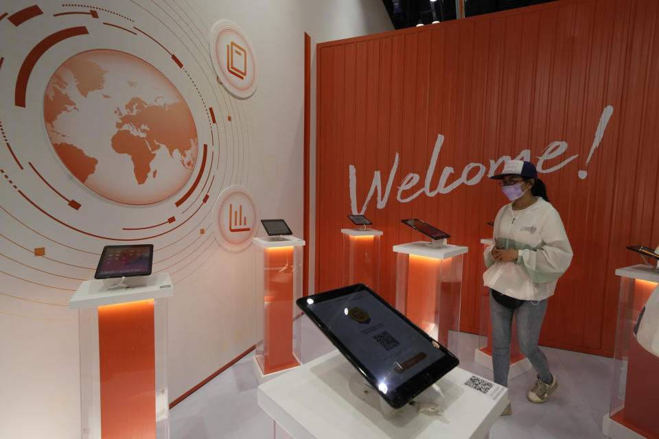 A visitor looks at digital devices promoting the services for Alibaba during the China International Fair for Trade in Services (CIFTIS) held in Beijing, China, Monday, Sept. 6, 2021. The ruling Communist Party's campaign to tighten control over China's industries and reduce use of foreign technology is slashing economic growth, a foreign business group warned Thursday, Sept. 22 and it appealed to Beijing to reverse course and open state-dominated markets wider. (AP Photo/Ng Han Guan)