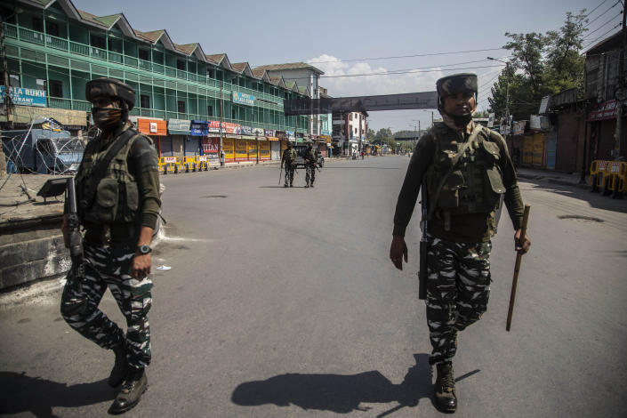 CORRECTS AGE - Indian paramilitary soldiers patrol a deserted market area in Srinagar, Indian controlled Kashmir, Thursday, Sept. 2, 2021. Indian authorities cracked down on public movement and imposed a near-total communications blackout Thursday in disputed Kashmir after the death of Syed Ali Geelani, a top separatist leader who became the emblem of the region's defiance against New Delhi. Geelani, who died late Wednesday at age 91, was buried in a quiet funeral organized by authorities under harsh restrictions, his son Naseem Geelani told The Associated Press. He said the family had planned the burial at the main martyrs' graveyard in Srinagar, the region's main city, as per his will but were disallowed by police. (AP Photo/ Mukhtar Khan)