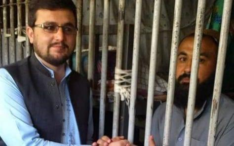 Muslim Afghan (left) shaking hands with a fellow prisoner in Kabul's Pul-e-Charkhi prison