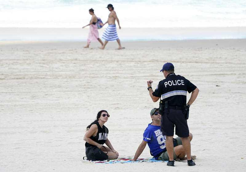 A policeman speaks with sunbathers on Surfers Paradise Beach on the Gold Coast.