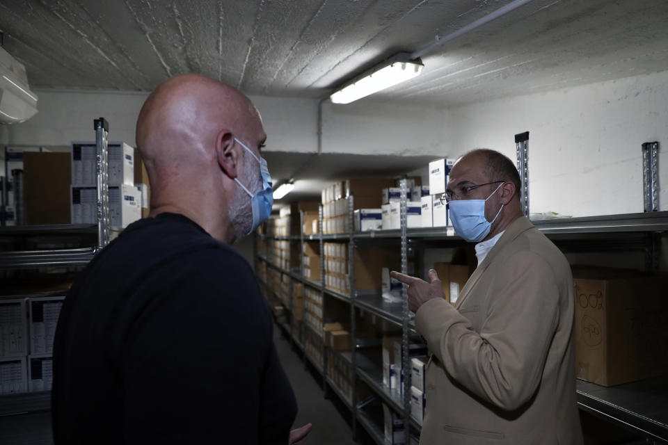 Caretaker Health Minister Hamad Hassan, right, inspects a medical warehouse in Beirut, Lebanon, Friday, June 11, 2021. Hassan raids warehouses in an effort to control those who are hoarding subsidized medical equipment and baby formula in order to sell them later at higher prices or on the black market. (AP Photo/Bilal Hussein)
