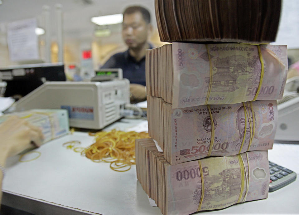 FILE - Vietnamese money dong is seen at the Asia Commercial Bank in Hanoi, Vietnam, in this June 16, 2008, file photo. The U.S. Treasury Department has branded Vietnam and Switzerland as currency manipulators while putting China and nine other countries on a watch list in an annual report designed to halt countries from manipulating their currencies to gain unfair trade advantages. (AP Photo/Chitose Suzuki, File)