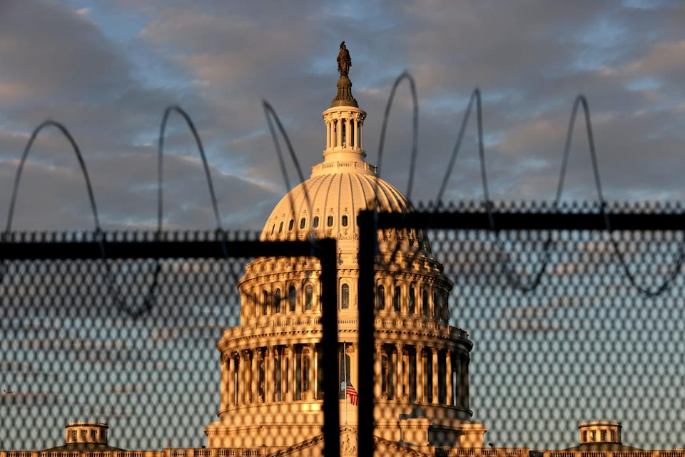 The U.S. Capitol is seen behind a fence with razor wire during sunrise on January 16, 2021 in Washington, DC.