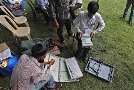 Polling officers check an Electronic Voting Machine (EVM) after collecting it from a distribution centre ahead of general elections in Jorhat district, in the northeastern Indian state of Assam April 6, 2014. REUTERS/Adnan Abidi