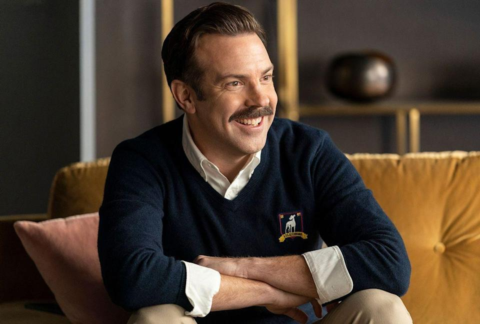 """<p><em>Ted Lasso </em>is set in a world in which teamwork is rewarded, friendship is paramount, and kindness is always the best way forward. Yep, it's a cozy, feel-good cocoon. In the series, Jason Sudeikis plays Ted Lasso, an American football coach who takes a gig with an English soccer team, despite knowing nothing about the sport. He's armed only with his goofy sense of humor and disarming way of connecting with people—and it turns out, that might be enough to win. Listening to Ted Lasso's (Jason Sudeikis) inspiring speeches, it's hard not to feel like he's talking to <em>you</em>, as opposed to his soccer team. </p><p><a class=""""link rapid-noclick-resp"""" href=""""https://go.redirectingat.com?id=74968X1596630&url=https%3A%2F%2Ftv.apple.com%2Fus%2Fepisode%2Fpilot%2Fumc.cmc.zb0yksqtym68hasbq8mj4jwp%3Faction%3DplaySmartEpisode&sref=https%3A%2F%2Fwww.redbookmag.com%2Flife%2Fg37608731%2Fhappy-feel-good-tv-shows%2F"""" rel=""""nofollow noopener"""" target=""""_blank"""" data-ylk=""""slk:Watch Now"""">Watch Now</a></p>"""