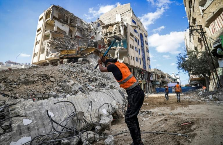 A Palestinian workman breaks rubble from a Gaza City building destroyed during the May conflict between Hamas and Israel