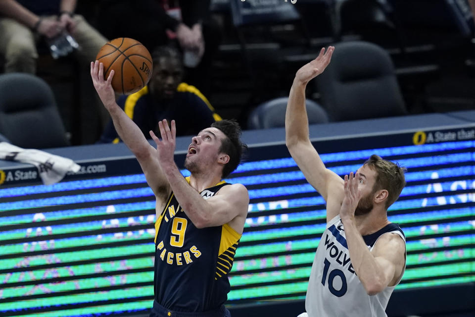 Indiana Pacers' T.J. McConnell (9) puts up a shot against Minnesota Timberwolves' Jake Layman (10) during the first half of an NBA basketball game, Wednesday, April 7, 2021, in Indianapolis. (AP Photo/Darron Cummings)
