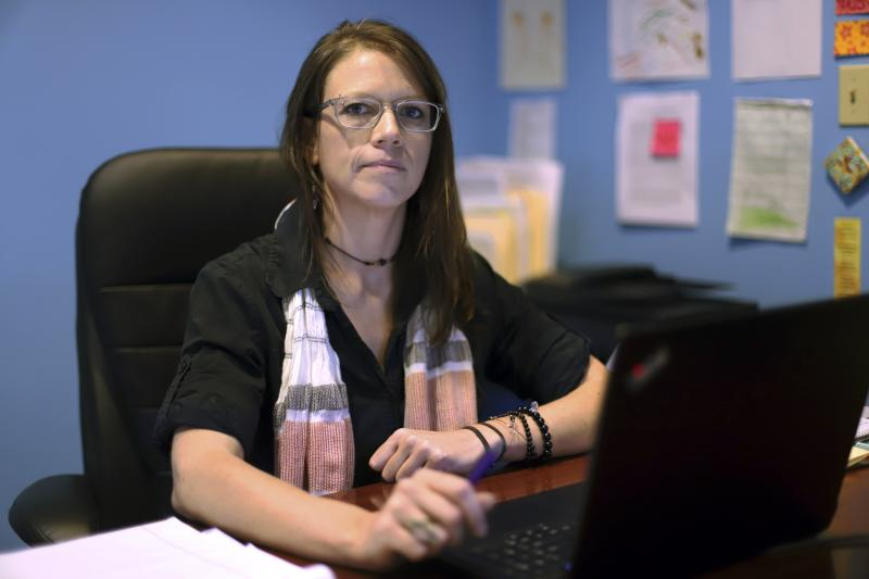 In this Oct. 1, 2019, photo, Michaela Fissel, executive director of Advocacy Unlimited, sits at her desk in her office in New Britain, Conn. Fissel thinks changes to safety standards at hospital psychiatric units are making the environment harsher for the patients. (AP Photo/Chris Ehrmann)