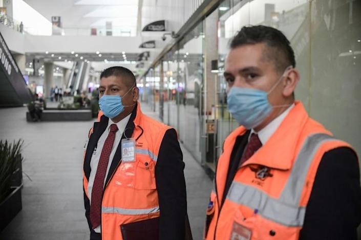 Employees wear face masks at Mexico City International Airport. Several Latin American states have tightened travel restrictions due to the coronavirus outbreak (AFP Photo/Pedro PARDO)