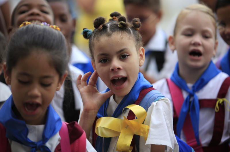 Students wearing yellow ribbons sing during a ceremony commemorating the 15th anniversary of the arrest of five Cuban agents in the U.S. at the start of their school day in Havana, Cuba, Thursday, Sept. 12, 2013. Rene Gonzalez, one of the five who was freed in 2011, called for people to wear and hang yellow ribbons to press for the release of the four others still in U.S. prisons who were convicted of spying. (AP Photo/Franklin Reyes)