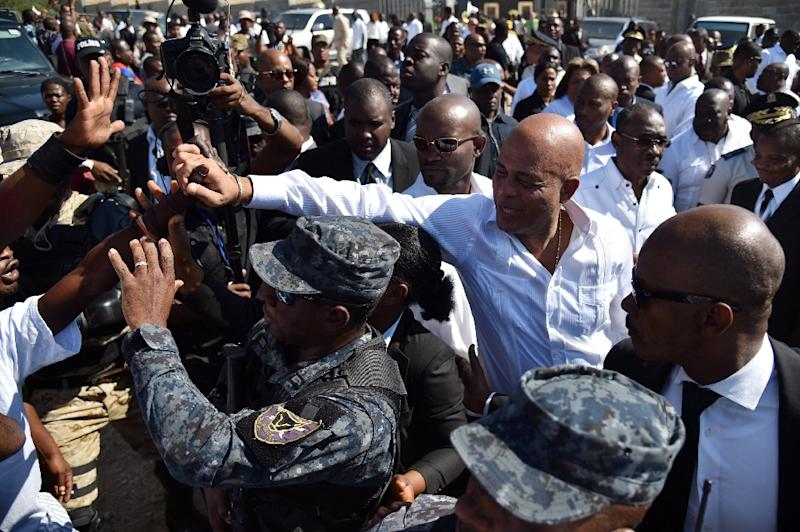 Haitian President Michel Martelly greets supporters after placing flowers during a memorial ceremony on January 12, 2016 in Port-au-Prince (AFP Photo/Hector Retamal)
