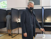 Lithuania's President Gitanas Nauseda, wearing face masks to protect against coronavirus, casts his ballot at a polling station during the parliamentary elections in Vilnius, Lithuania, Sunday, Oct. 11, 2020. Polls opened Sunday for the first round of national election in Lithuania, where voters will renew the 141-seat parliament and the ruling four-party coalition is widely expected to face a stiff challenge from the opposition to remain in office. (Lithuanian President Office via AP)