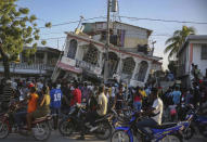 FILE - In this Aug. 14, 2021 file photo, residents gather outside the Petit Pas Hotel, destroyed by a 7.2 earthquake, in Les Cayes, Haiti. Haitians continue to show up at hospitals seeking care for injuries almost two weeks after an earthquake battered their country. (AP Photo/Joseph Odelyn, File)