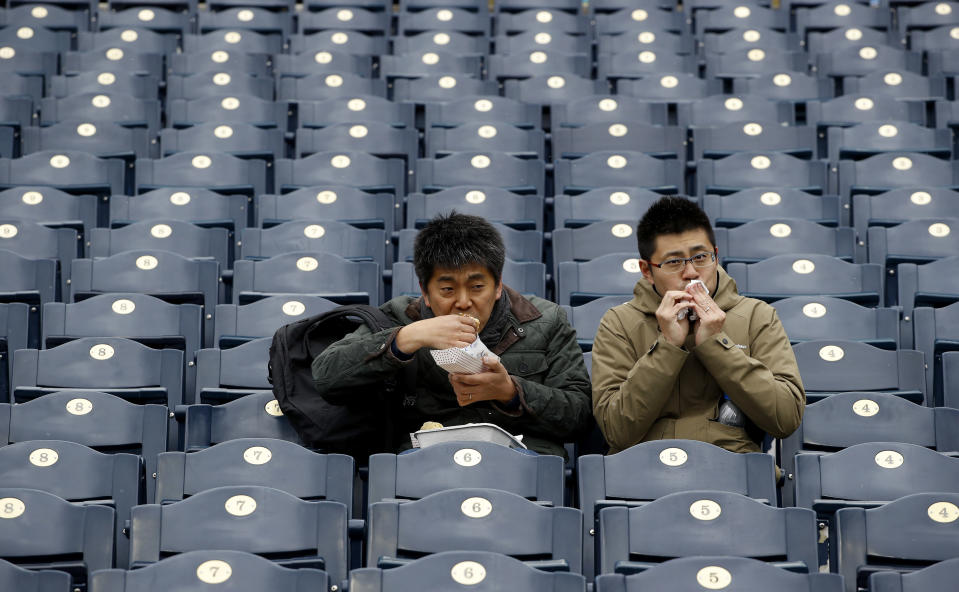 FILE - In this April 15, 2018, file photo, fans finish their food before exiting Kauffman Stadium after a baseball game between the Kansas City Royals and the Los Angeles Angels was postponed due to inclement weather in Kansas City, Mo. As lock-downs are lifted, restrictions on social gatherings eased and life begins to resemble some sense, sports are finally starting to emerge from the coronavirus pandemic. When stadiums do reopen for fans, how are teams going to drive them through the gate? (AP Photo/Charlie Riedel, File)