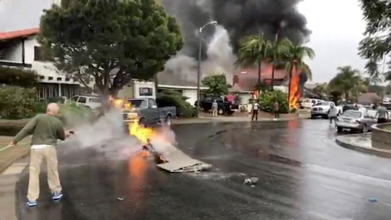 A man puts out fire on a piece of debris from a plane that crashed into a house in a residential neighborhood in Yorba Linda, Calif., Feb. 3, 2019, in this still image from video obtained from social media. (Photo: Joshua Nelson/via Reuters)
