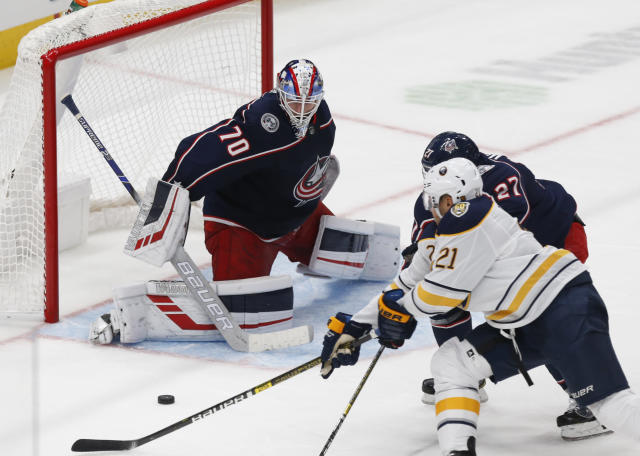 Columbus Blue Jackets goalie Joonas Korpisalo, left, of Finland, stops a shot by Buffalo Sabres forward Kyle Okposo, right, as Blue Jackets defenseman Ryan Murray defends during the third period of an NHL hockey game in Columbus, Ohio, Monday, Oct. 7, 2019. (AP Photo/Paul Vernon)