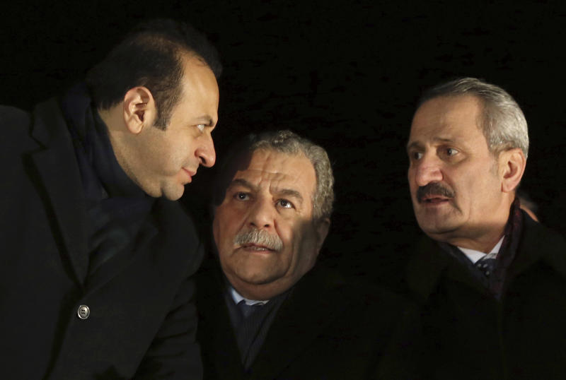 In this photo taken late Tuesday, Dec. 24, 2013, Turkey's Economy Minister Zafer Caglayan, right, Interior Minister Muammer Guler, center, and EU Affairs Minister Egemen Bagis speak at the Esenboga Airport in Ankara, Turkey. Guler and Caglayan resigned from their posts on Wednesday, Dec. 25, 2013, days after their sons were arrested in a massive corruption and bribery scandal that has targeted Prime Minister Recep Tayyip Erdogan's allies and has become the worst crisis in his decade in power. Caglayan and Guler both stepped down on Wednesday, despite denying any wrongdoing. (AP Photo)
