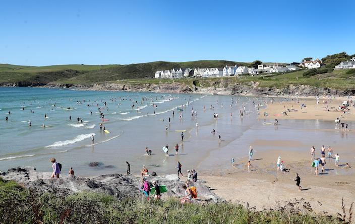 Beachgoers enjoy Polzeath beach in Cornwall as the UK experiences a heatwave. (PA)