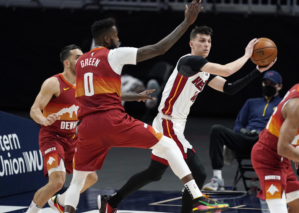 Miami Heat guard Tyler Herro, right, passes the ball as Denver Nuggets forward JaMychal Green defends during the first half of an NBA basketball game Wednesday, April 14, 2021, in Denver. (AP Photo/David Zalubowski)