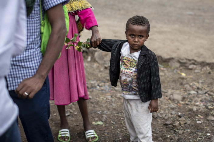 A young boy carries flowers as Ethiopian Orthodox Christians celebrate Easter Sunday in Gondar, in the Amhara region of Ethiopia Sunday, May 2, 2021. Ethiopia faces a growing crisis of ethnic nationalism that some fear could tear Africa's second most populous country apart, six months after the government launched a military operation in the Tigray region to capture its fugitive leaders. (AP Photo/Ben Curtis)