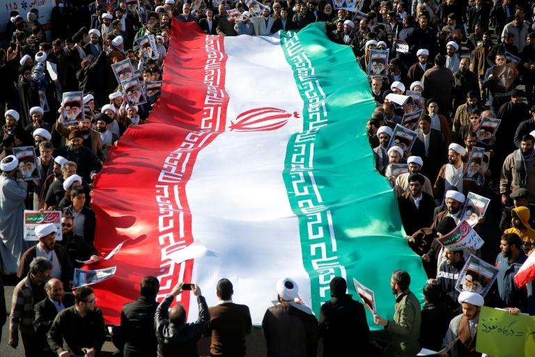 Pro-government demonstrators with a huge national flag march in Iran's holy city of Qom on January 3, 2018