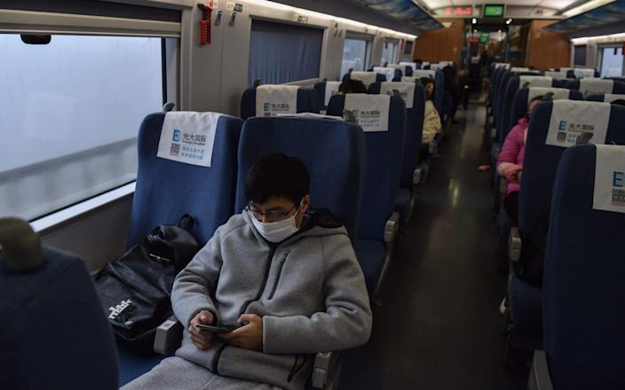 A young man wearing a protective facemask sits on a train usually full with passengers ahead of the Lunar New Year as he travels from the Chinese city of Shanghai to his hometown of Wuhan - AFP