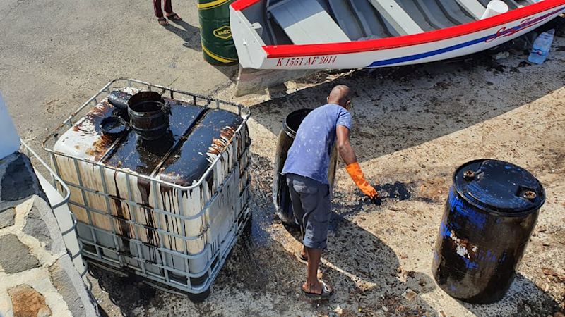 Shot from above, a man cleans up the oil, dumping it in a barrel.