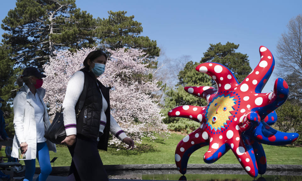 """People walk by the sculpture """"I Want to Fly to the Universe"""" by Japanese artist Yayoi Kusama at the New York Botanical Garden, Thursday, April 8, 2021 in the Bronx borough of New York. The expansive exhibit has opened, and ticket sales have been brisk in a pandemic-weary city hungry for more outdoor cultural events. (AP Photo/Mark Lennihan)"""