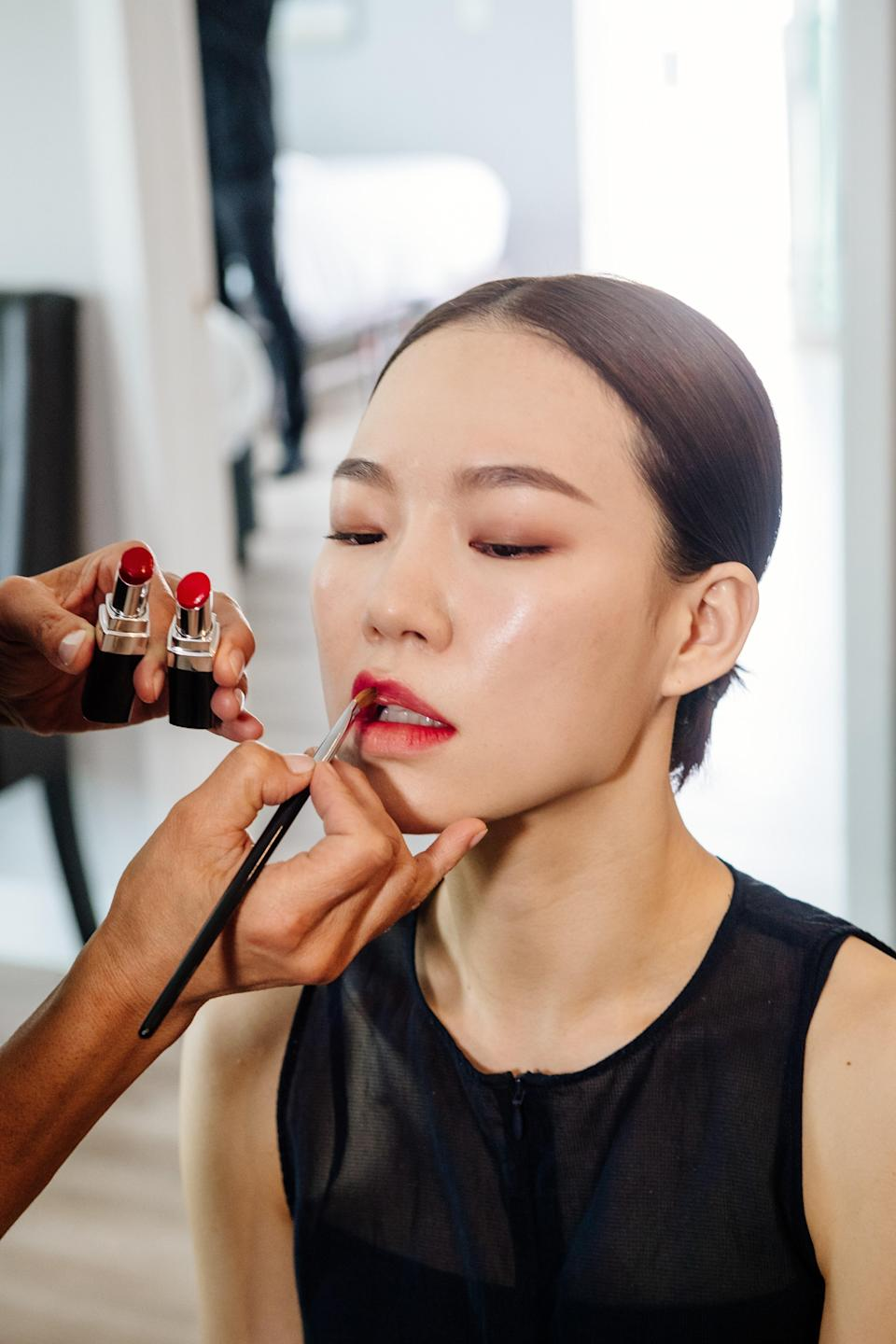 """""""I gave her skin a glassy, modern glow with a two-toned ombré lip keeping it extra fresh,"""" explains Bua. Han's crimson pout was achieved with a swipe of <a href=""""https://www.chanel.com/us/makeup/p/172118/rouge-coco-bloom-hydrating-plumping-intense-shine-lip-colour/"""" rel=""""nofollow noopener"""" target=""""_blank"""" data-ylk=""""slk:Chanel Rouge Coco Bloom in Magic"""" class=""""link rapid-noclick-resp"""">Chanel Rouge Coco Bloom in Magic</a> over the whole mouth, with deeper tone Vitalité layered on the center and slightly feathered out """"to keep the edges soft,"""" she says."""