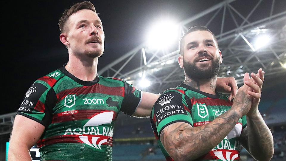 Damien Cook (pictured left) embraces teammate Adam Reynolds (pictured right).