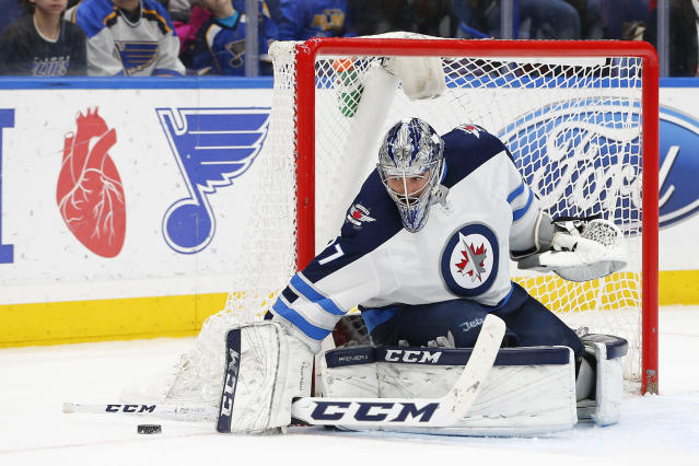 Winnipeg Jets goaltender Connor Hellebuyck stops a shot during the second period of an NHL hockey game against the St. Louis Blues, Friday, Feb. 23, 2018, in St. Louis. (AP Photo/Billy Hurst)