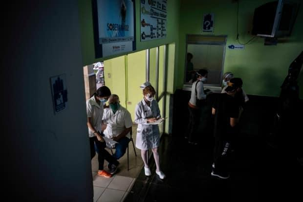 Healthcare workers run testing on volunteers of the Soberana-02 COVID-19 vaccine as part of Phase 3 of one of two experimental Cuban vaccines in Havana Wednesday, March 24, 2021.