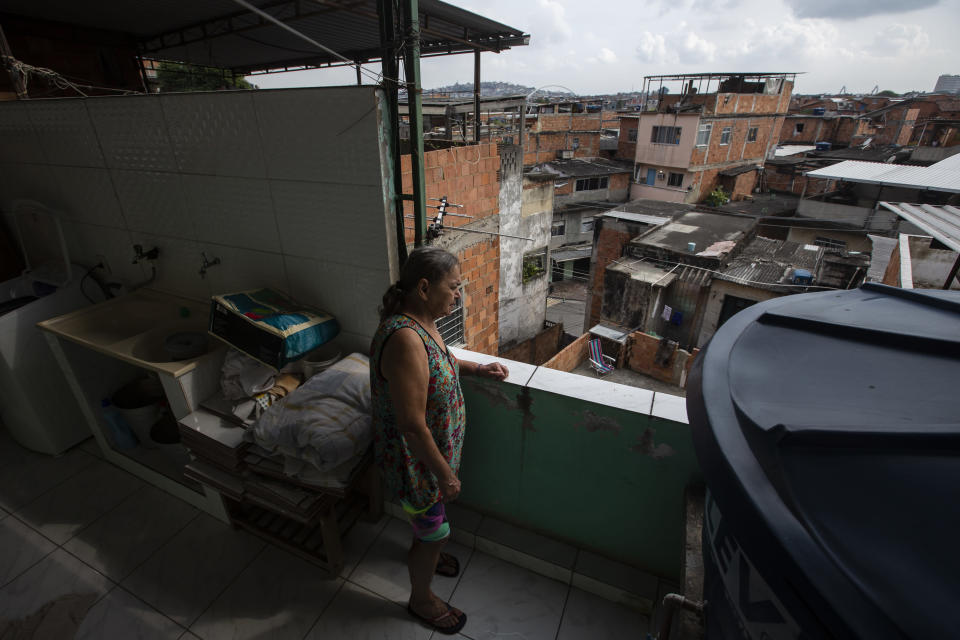 Diana dos Santos, 71, watches the movement of her neighborhood from her terrace home where she lives in social isolation, in the Mare neighborhood of Rio de Janeiro, Brazil, Saturday, Aug. 28, 2021, amid the new coronavirus pandemic. She refuses to leave her home until she gets a booster of the COVID-19 vaccine. (AP Photo/Bruna Prado)