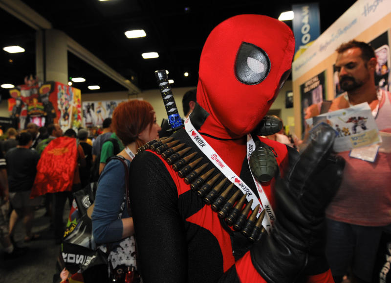 CORRECTS CHARACTER SUBJECT IS DRESSED AS TO DEADPOOL INSTEAD OF SPIDERMAN - Jonah Duhe, dressed as Deadpool, waits in line during the Preview Night event on Day 1 of the 2013 Comic-Con International Convention on Wednesday, July 17, 2013 in San Diego. (Photo by Denis Poroy/Invision/AP)