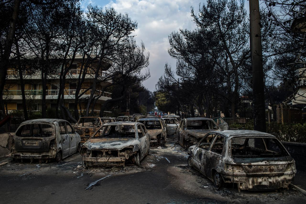 <p>This photo taken on July 24, 2018 show cars burnt following a wildfire at the village of Mati, near Athens, on July 24, 2018. Fifty people have died and 170 have been injured in wildfires ravaging woodland and villages in the Athens region, as Greek authorities rush to evacuate residents and tourists stranded on beaches along the coast on July 24, 2018. The death toll soared with a Red Cross official reporting the discovery of 26 bodies in the courtyard of a villa at the seaside resort of Mati. (Photo from Angelos Tzortzinis/AFP/Getty Images) </p>