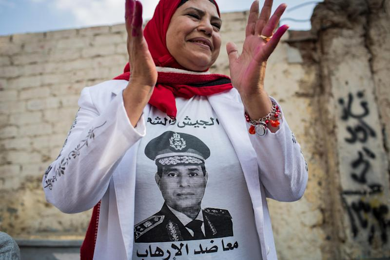 FILE - In this file photo taken Tuesday, Jan. 14, 2014, an Egyptian woman wears a t-shirt with a photo of Egypt's Defense Minister Gen. Abdel-Fattah el-Sissi outside a polling station on the first day of voting in the country's constitutional referendum in Cairo, Egypt. Former military chief Abdel-Fattah el-Sissi, if he wins Egypt's presidency as is widely expected, will have an overwhelming presence over a shattered political scene. Egypt's once dominant political force, the Muslim Brotherhood, is exhausted under a relentless crackdown. Non-Islamist parties are weak and largely acquiescent to his power. But the political vacuum is hardly a stable one. The Brotherhood is betting that with time the public will turn against el-Sissi. (AP Photo/Eman Helal, File)