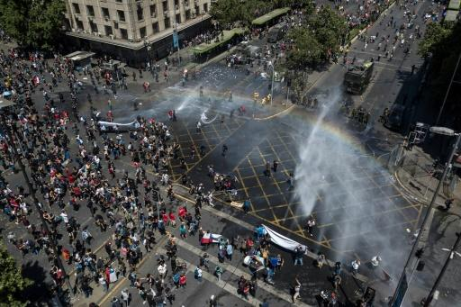 Riot police use water cannons on demonstrators in Santiago, on the sixth straight day of street violence in Chile, which has left at least 18 people dead