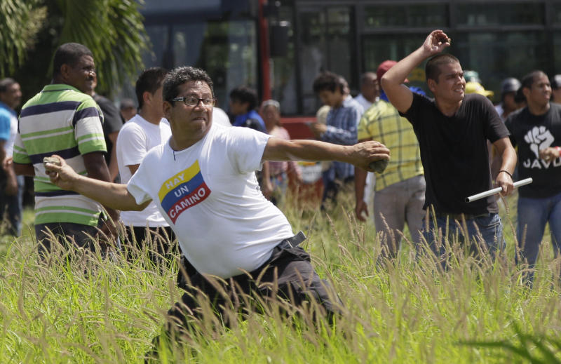 A supporter of opposition presidential candidate Henrique Capriles hurls stones at supporters of Venezuela's President Hugo Chavez, not seen, who were hurling stones back, before an opposition campaign event started at the International airport in Puerto Cabello, Venezuela, Wednesday, Sept. 12, 2012. Tensions have sporadically erupted into violent clashes and scuffles between supporters of the two candidates ahead of the Oct. 7 presidential vote. (AP Photo/Ariana Cubillos)