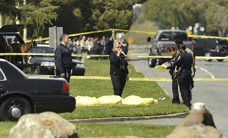 """In this April 2, 2012 file photo, Oakland police work after a school shooting at Oikos University in Oakland, Calif., Monday, April 2, 2012. Minutes after the shooting near the Oakland Airport and the supposed gunman on the lam, police Sgt. Chris Bolton used social media site Nixle to text a flurry of alerts to thousands through an emerging social media notification provider. """"Stay out of area,"""" one alert said. """"Multiple shooting victims reported. Medical on-scene. Police are evacuating a nearby, affected business."""" (AP Photo/Noah Berger, File)"""