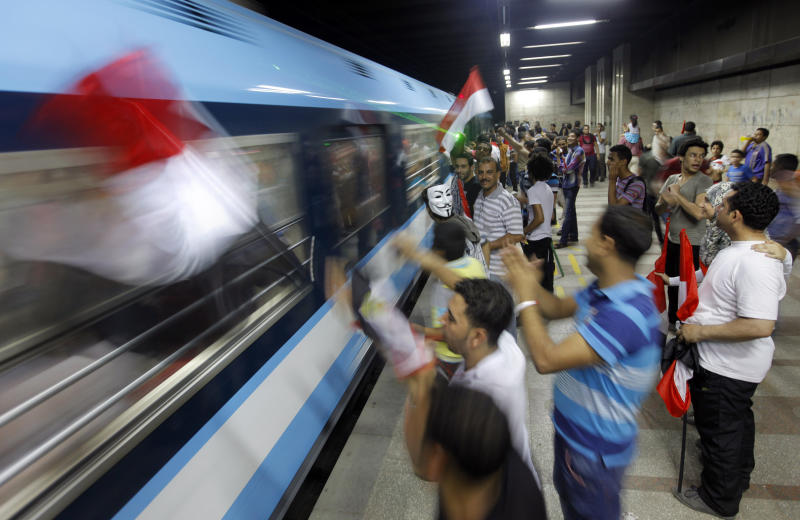 In this image made late Wednesday, July 3, 2013, opponents of Egypt's Islamist leader Mohammed Morsi wave national flags to a passing underground train as they celebrate Morsi's ouster in Cairo, Egypt. The chief justice of Egypt's Supreme Constitutional Court was sworn in Thursday as the nation's interim president, taking over hours after the military ousted the Islamist President Mohammed Morsi. Adly Mansour took the oath of office at the Nile-side Constitutional Court in a ceremony broadcast live on state television. According to military decree, Mansour will serve as Egypt's interim leader until a new president is elected. A date for that vote has yet to be set. (AP Photo/Amr Nabil)
