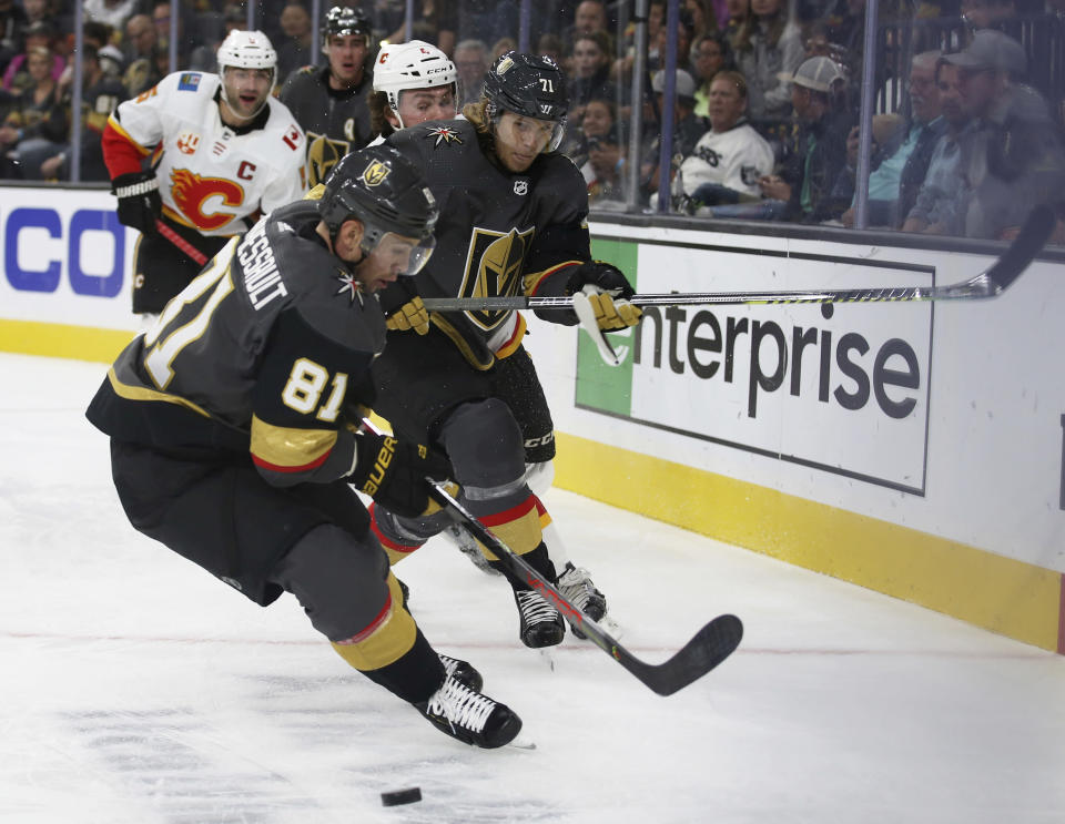 Vegas Golden Knights center Jonathan Marchessault (81) fights for control of a loose puck with teammate William Karlsson (71) during the second period of the team's NHL hockey game against the Calgary Flames on Saturday, Oct. 12, 2019, in Las Vegas. (AP Photo/Benjamin Hager)