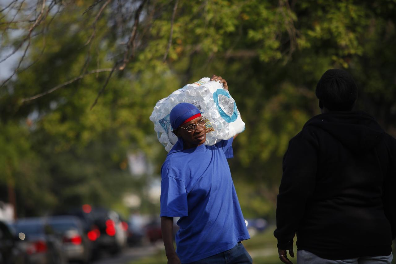 "A resident carries a case of water outside Waite High School in Toledo, Ohio, August 3, 2014. Some 500,000 residents in and around Toledo, Ohio were without safe drinking water for a second day on Sunday while local water supplies were being tested following the discovery of high toxin levels from algae on Lake Erie. Health officials sent samples to several laboratories on Saturday for testing after finding Lake Erie may have been affected by a ""harmful algal bloom,"" but results would not return until Sunday, Ohio Environmental Protection Agency spokeswoman Heidi Griesmer said. The lake provides the bulk of the area's drinking water. REUTERS/Joshua Lott (UNITED STATES - Tags: DISASTER ENVIRONMENT)"