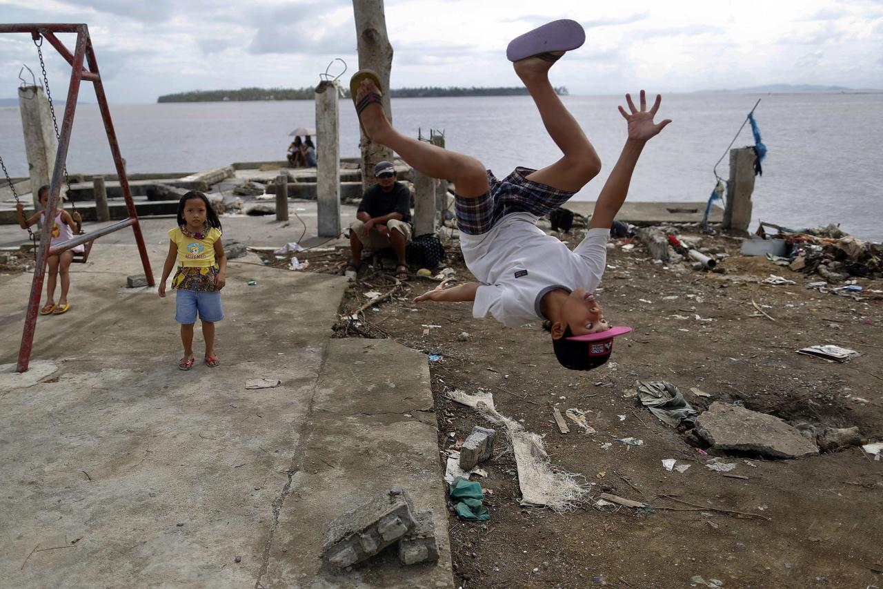 John Dave Galang, a survivor of Typhoon Haiyan, shows his acrobatic skills at a devastated area of Basey, north of Tacloban November 19, 2013. Authorities estimate more than 3,900 people were killed when Typhoon Haiyan, one of the largest ever recorded, made landfall in the central Philippines and the sea surged ashore. Philippine authorities, the U.S. military and international agencies face a mounting humanitarian crisis, with the number of people displaced by the catastrophe estimated at four million, up from 900,000 late last week. REUTERS/Damir Sagolj (PHILIPPINES - Tags: DISASTER ENVIRONMENT SOCIETY)