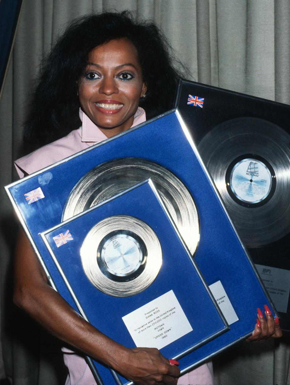 Diana Ross receives an award for the sale of her Motown single 'Upside Down' during a visit to England in 1980 in London, England. (Photo by Anwar Hussein/Getty Images)