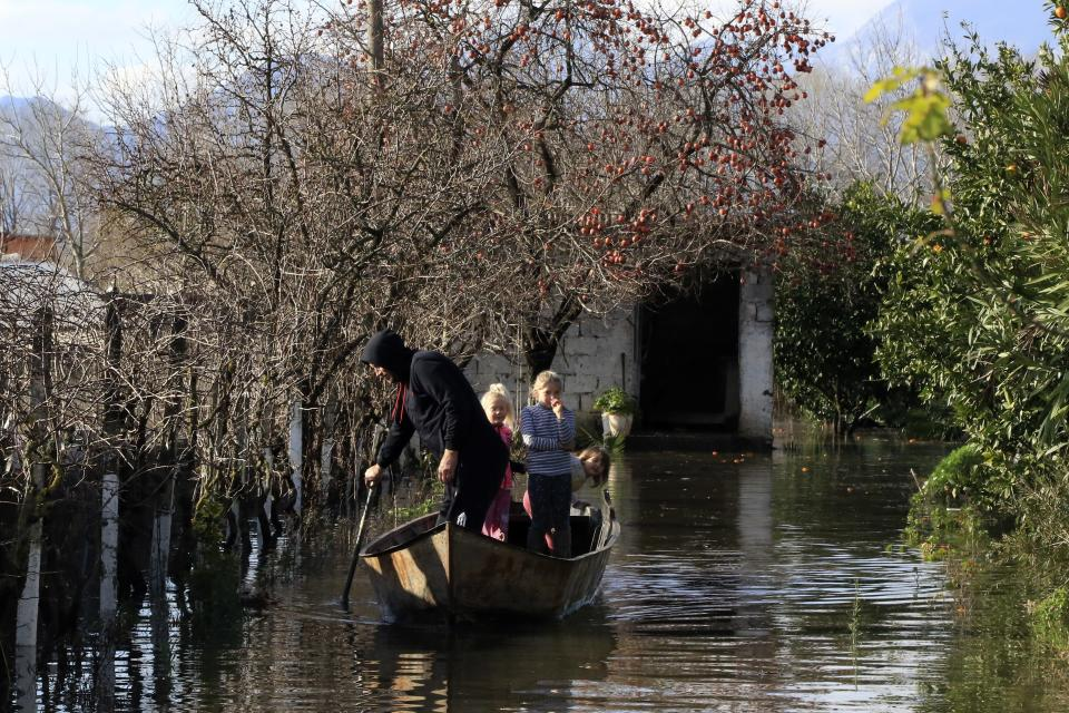 A man with children use a dinghy after heavy rainfalls in Obot village, about 100 kilometres (60 miles) northwest of Tirana, Albania, Monday, Jan. 11, 2021. Heavy rainfall and snow during the last days has flooded many areas in the country, authorities said on Monday. Thousands of hectares (acres) have been flooded in western Albania where authorities have evacuated scores of them. (AP Photo/Hektor Pustina)