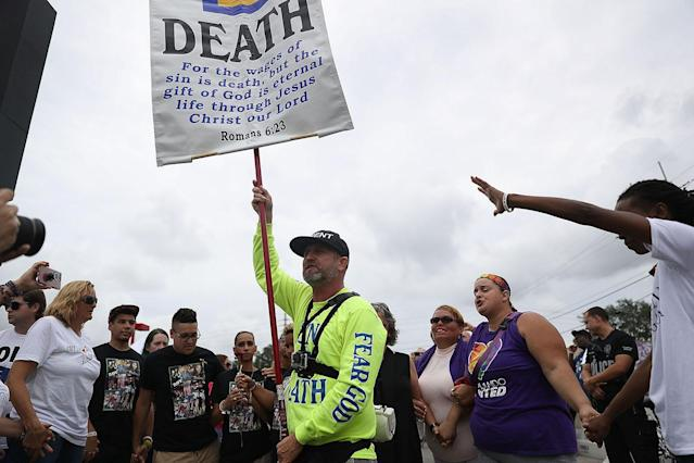 """<p>Mourners circle around a man protesting against homosexuality with some chanting """"Love overcomes Hate"""" outside the Pulse gay nightclub as a memorial service was being held for the one-year anniversary of a mass shooting at the club on June 12, 2017 in Orlando, Florida. (Joe Raedle/Getty Images) </p>"""